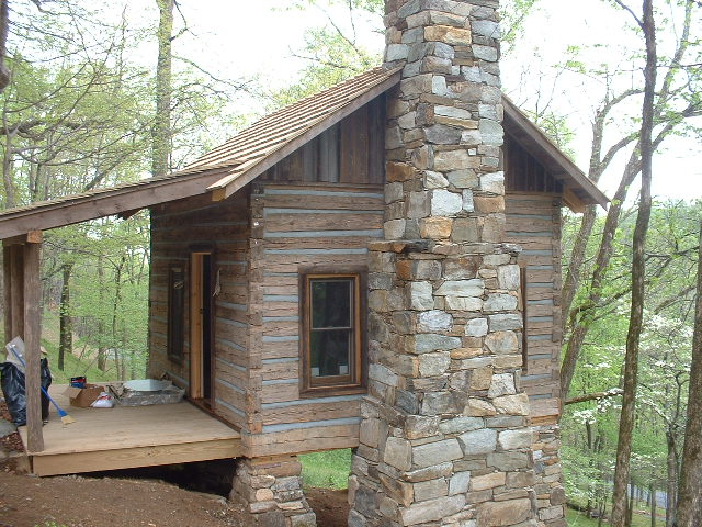 Exterior finishes: The completed cabin, with massive stone chimney. Original cabins often had large dry-stacked chimneys which were used for heat and cooking.